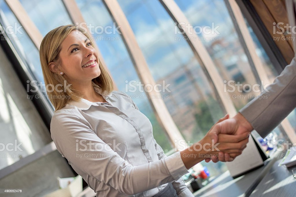 Business woman greeting a client at the office stock photo