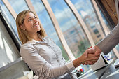 Business woman greeting a client at the office