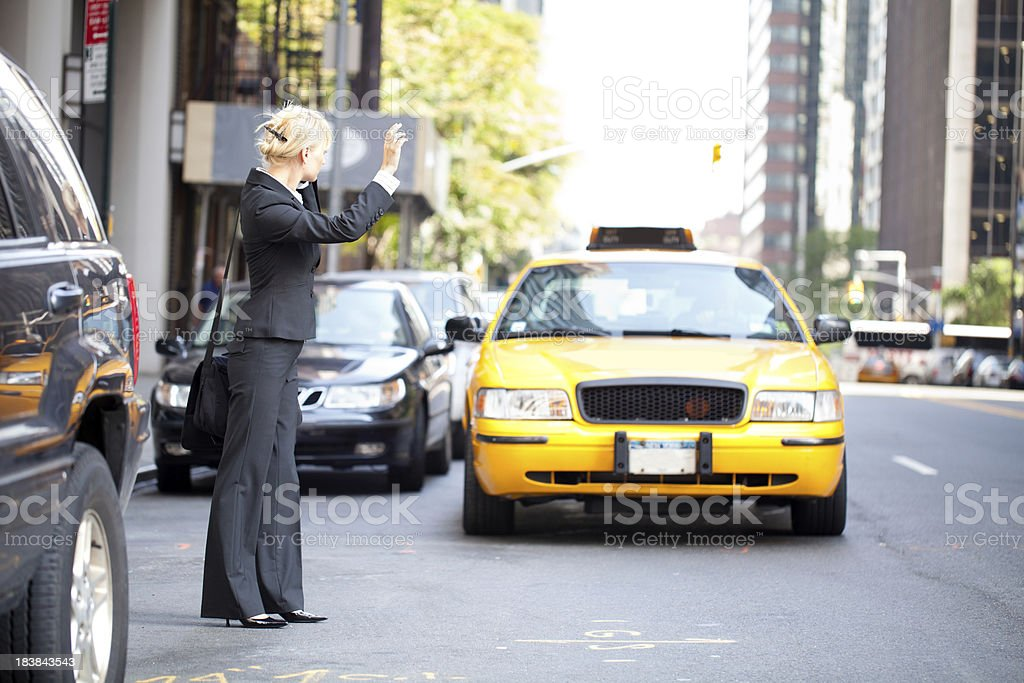 Business woman hailing yellow taxi cab in city stock photo