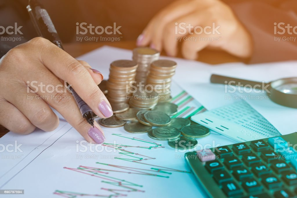 business woman hand analyzing financial data, business graph with pile of coins ,stock chart in background stock photo