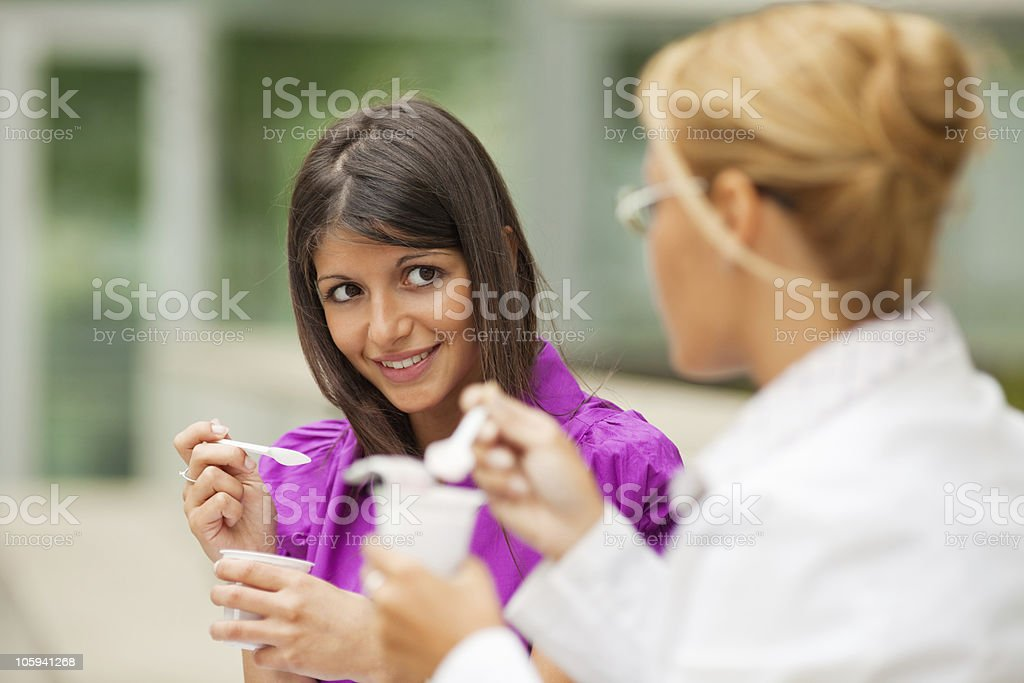 Business woman having a chat and eating yogurt outside royalty-free stock photo