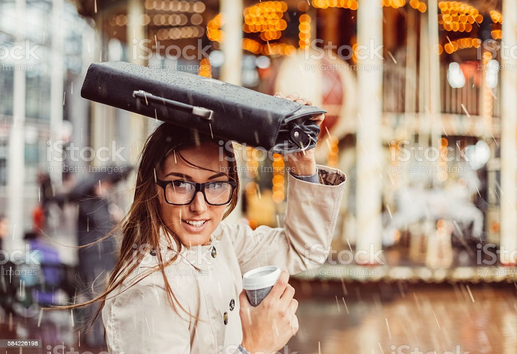 Business woman hiding from the rain stock photo