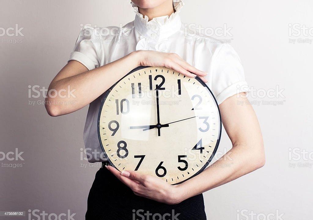 A business woman holding a large clock stock photo