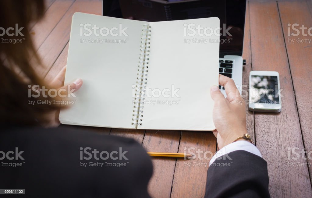 Business woman holding blank notebook with laptop and cell phone. stock photo