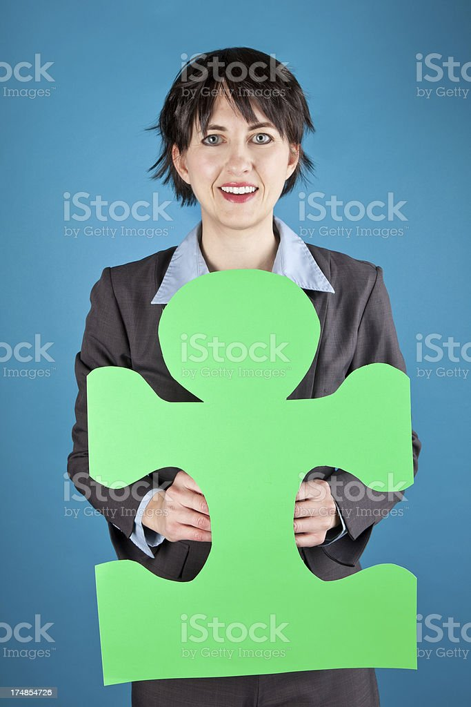 Business Woman Holding Green Puzzle Piece stock photo