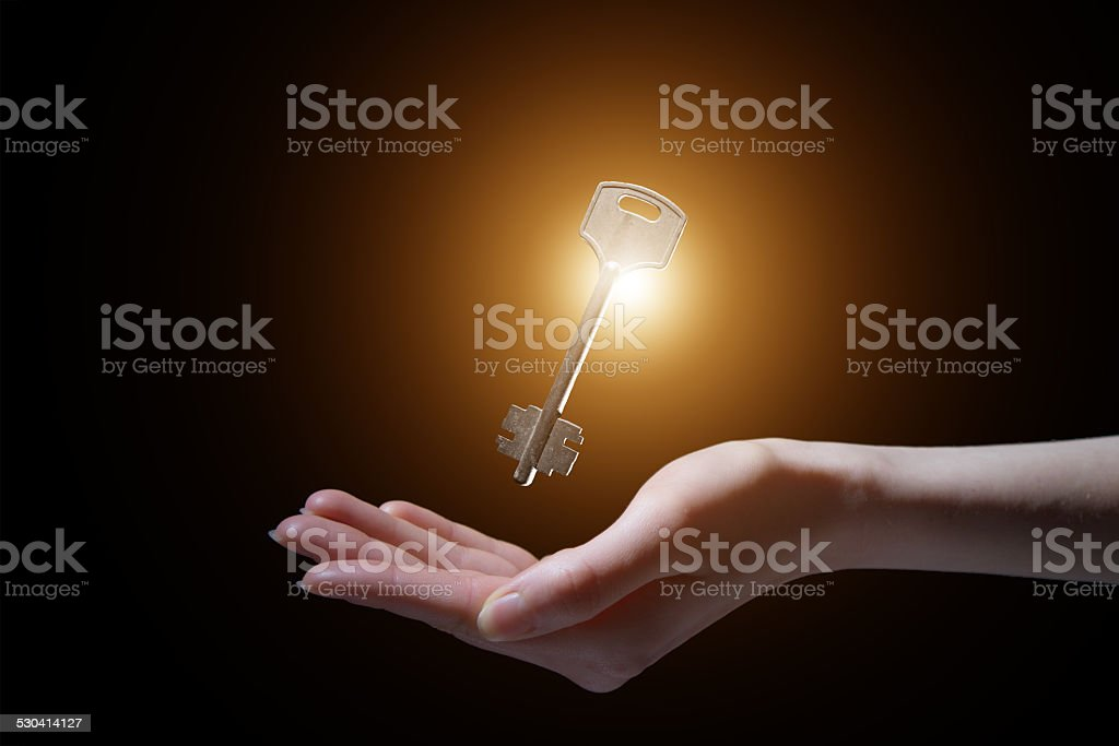 business woman holding shining key in a dark stock photo