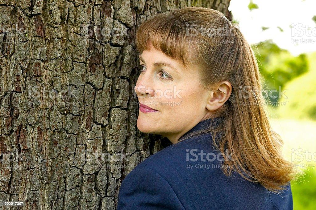 Femme d'affaires se tenant un arbre et écoute photo libre de droits