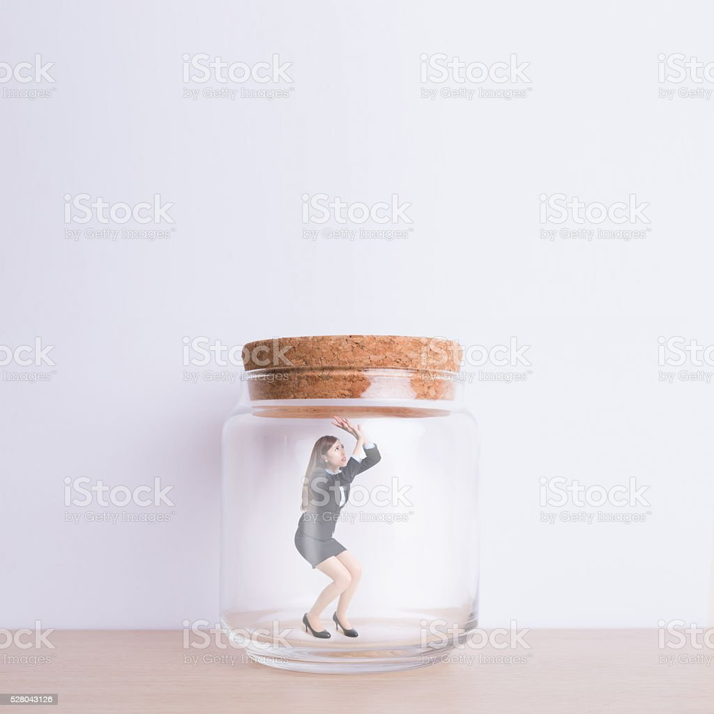 business woman imprisoned in jar stock photo