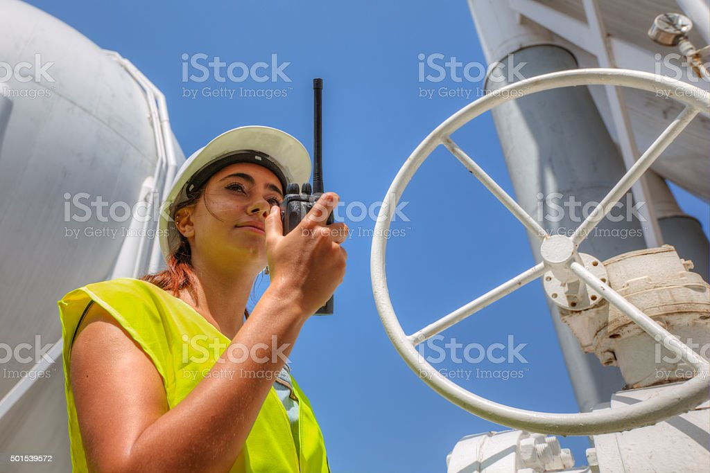 Business woman in a refinery talking on radio stock photo