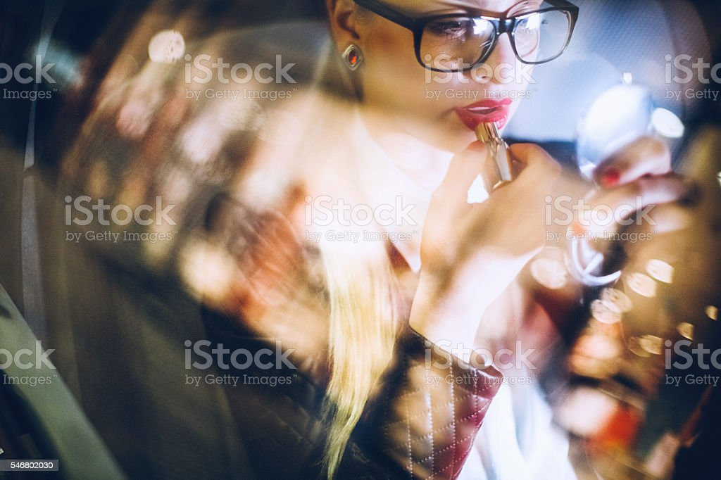 Business woman in car on Paris streets putting lipstick on stock photo