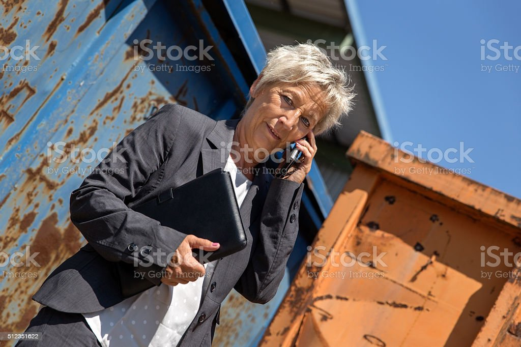 Business woman in front of containers is calling with smartphone stock photo