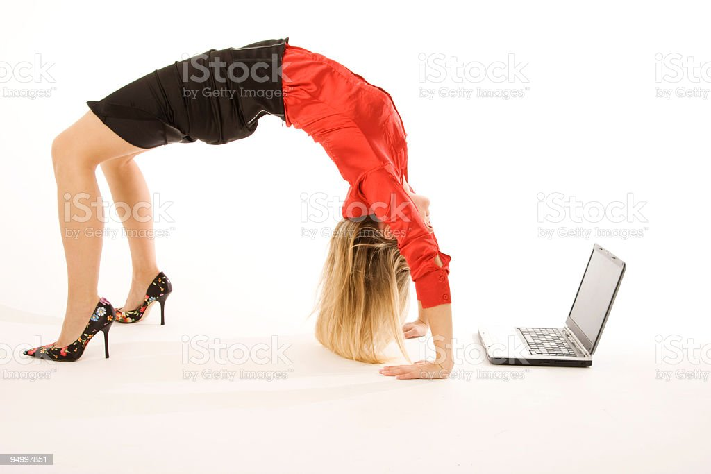 Business woman in heels doing back bend near laptop stock photo