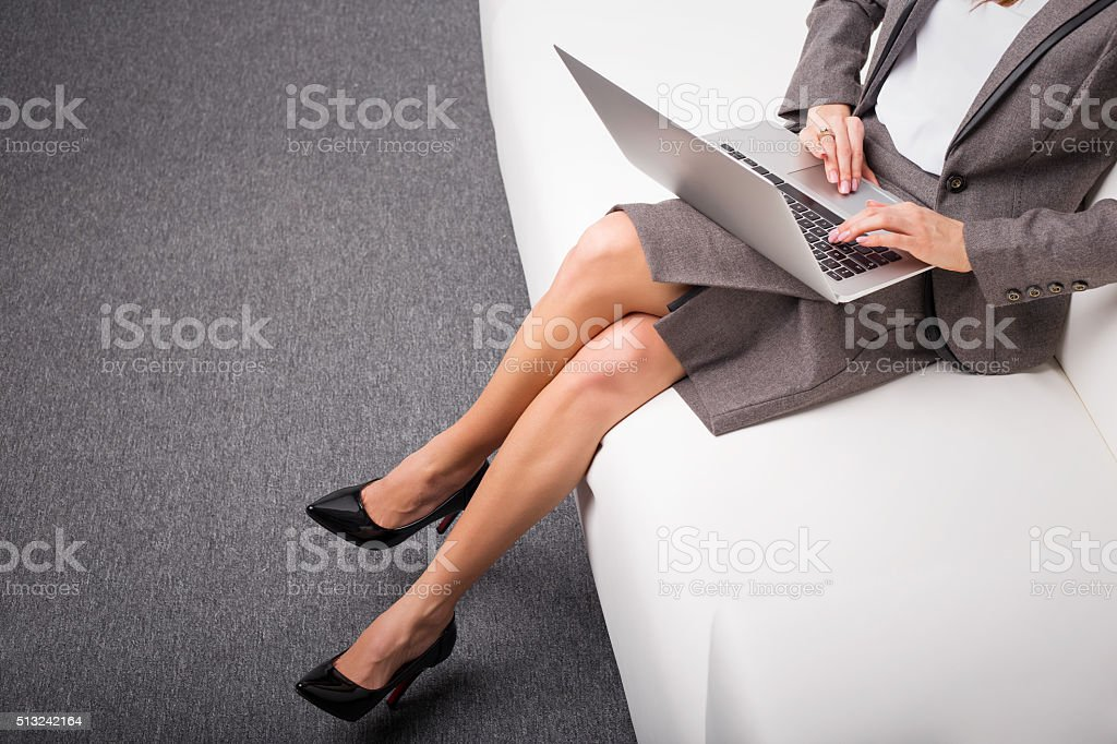 Business woman in high heels sitting on sofa stock photo