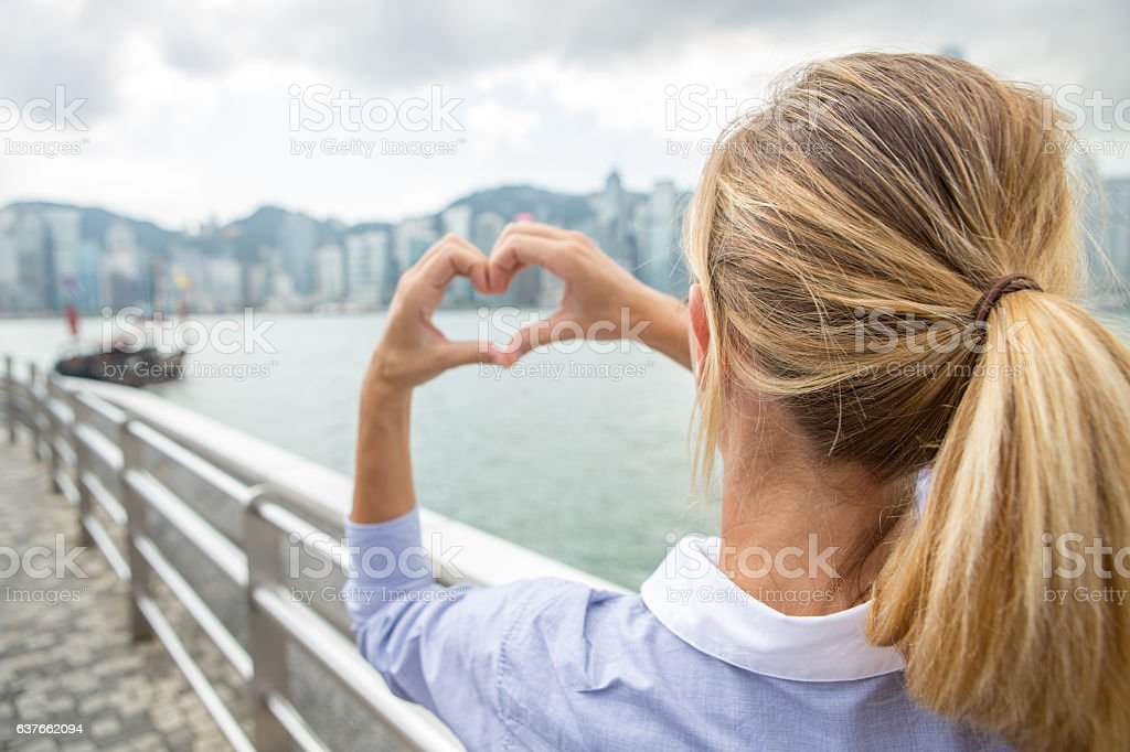 Business woman in Hong Kong makes heart shape finger frame stock photo
