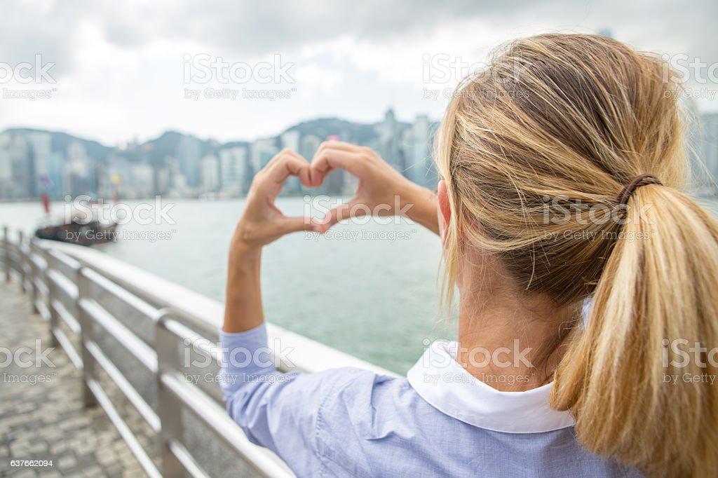 Business woman in Hong Kong makes heart shape finger frame stock photo