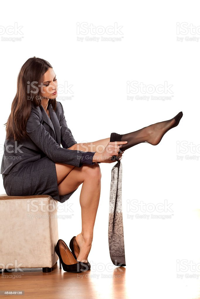 Business woman in jacket and skirt puts on nylon stockings stock photo