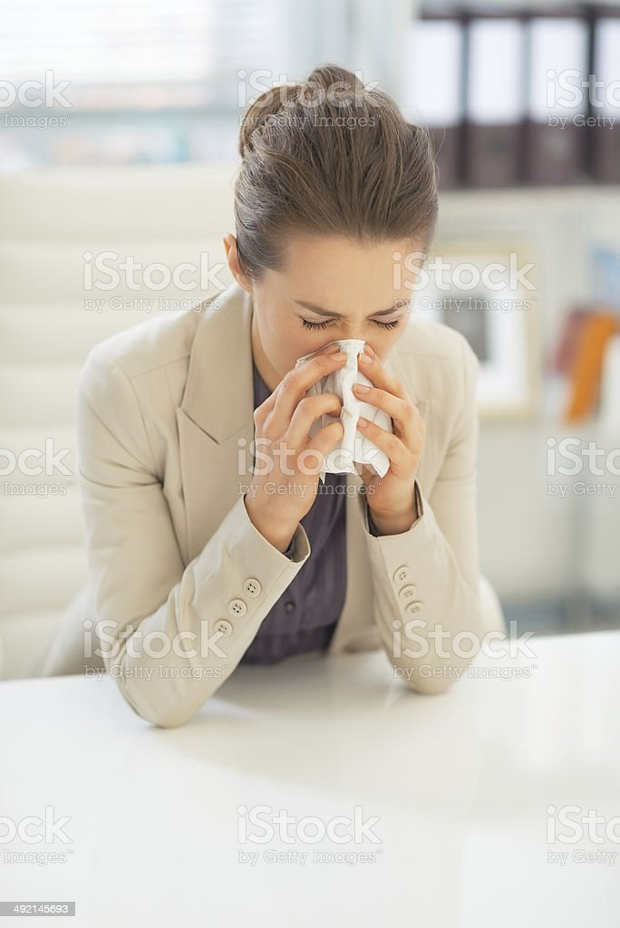 business woman in office blowing nose royalty-free stock photo