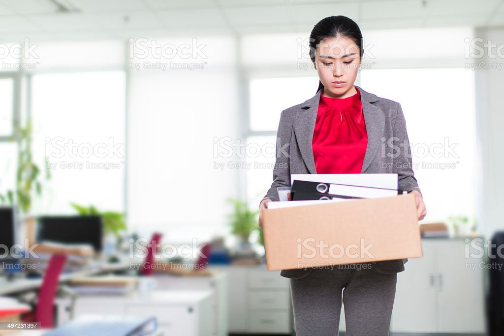 Business woman in office carrying full box stock photo
