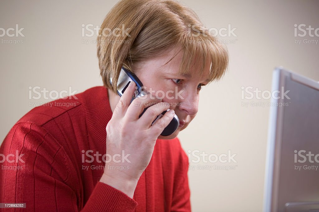 business woman in red on cell and laptop stock photo