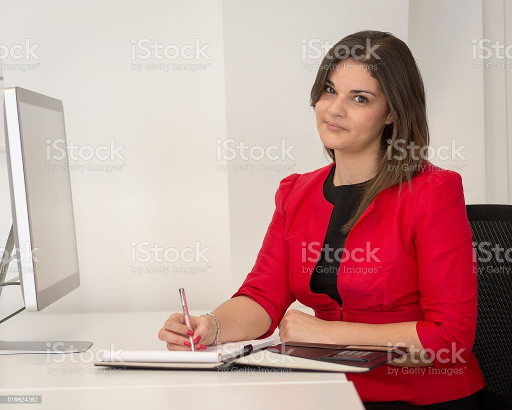 Business Woman In Red Waist Coat Writing Notes stock photo