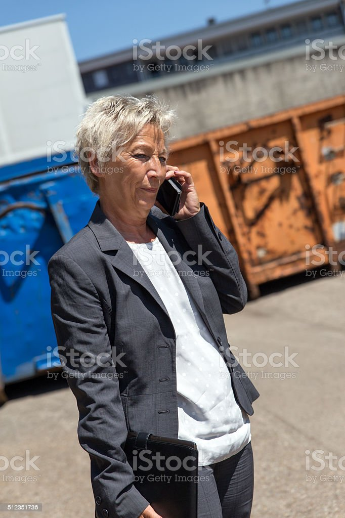 Business woman is calling in front of containers stock photo