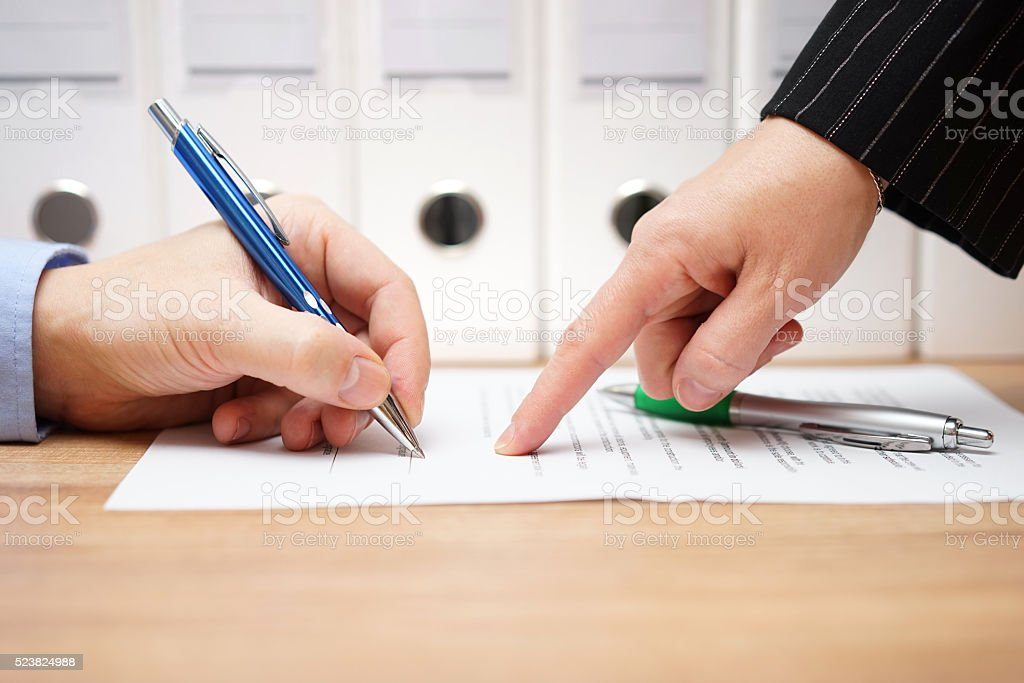 business woman is pointing where to sign on document, stock photo