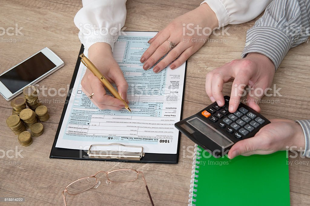 business woman is reviewing 1040 tax form with taxconsultant stock photo
