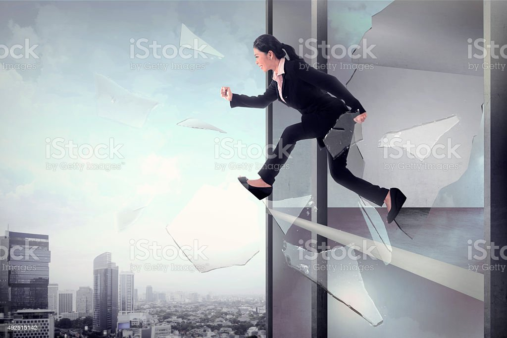 Business woman jump through office window glass stock photo