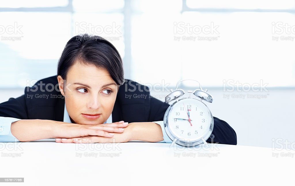 Business woman looking at alarm clock on desk royalty-free stock photo