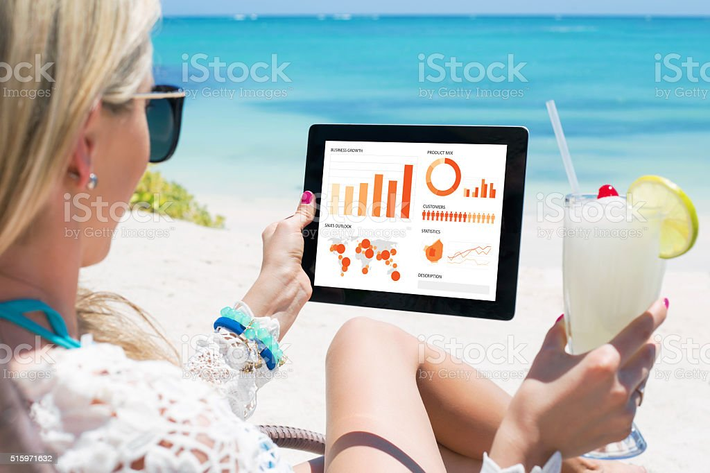 Business woman looking at graphs and charts on digital tablet stock photo