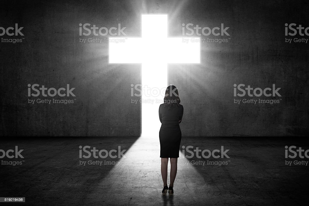 Business woman looking the shining cross on the wall stock photo
