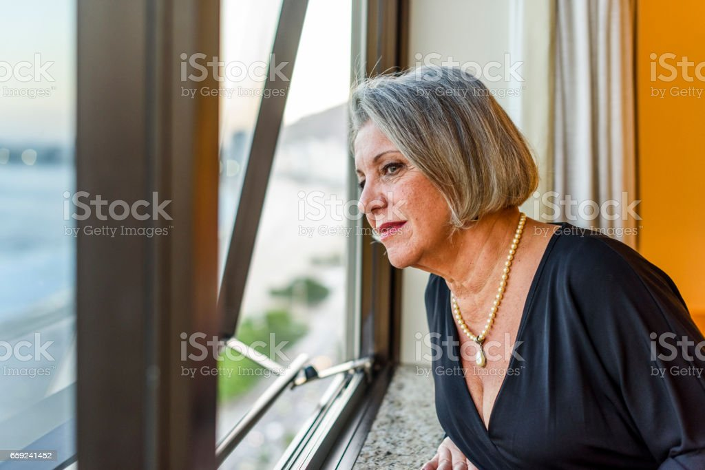 Business woman looking through the window of her hotel room stock photo