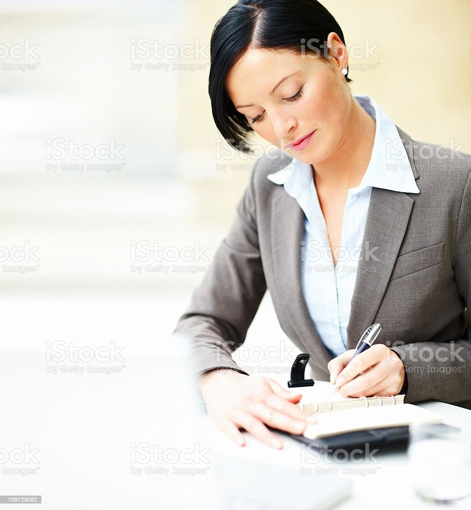 Business woman making a note in black book royalty-free stock photo