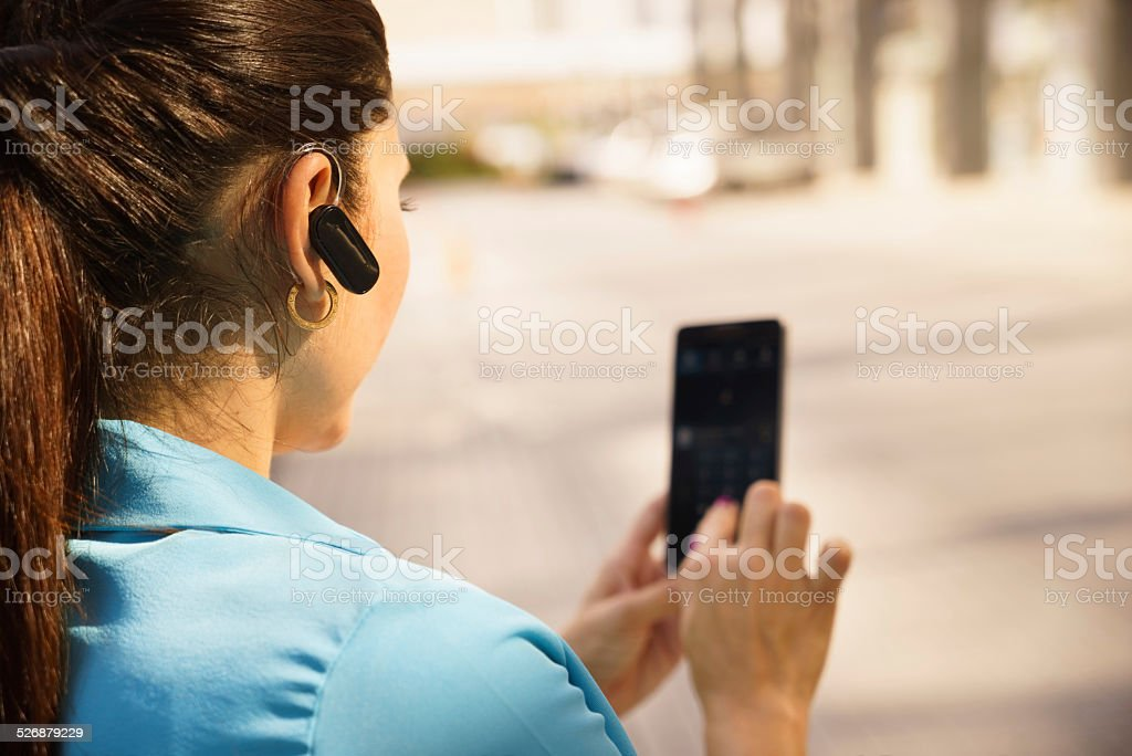 Business woman making a phone call with bluetooth device stock photo