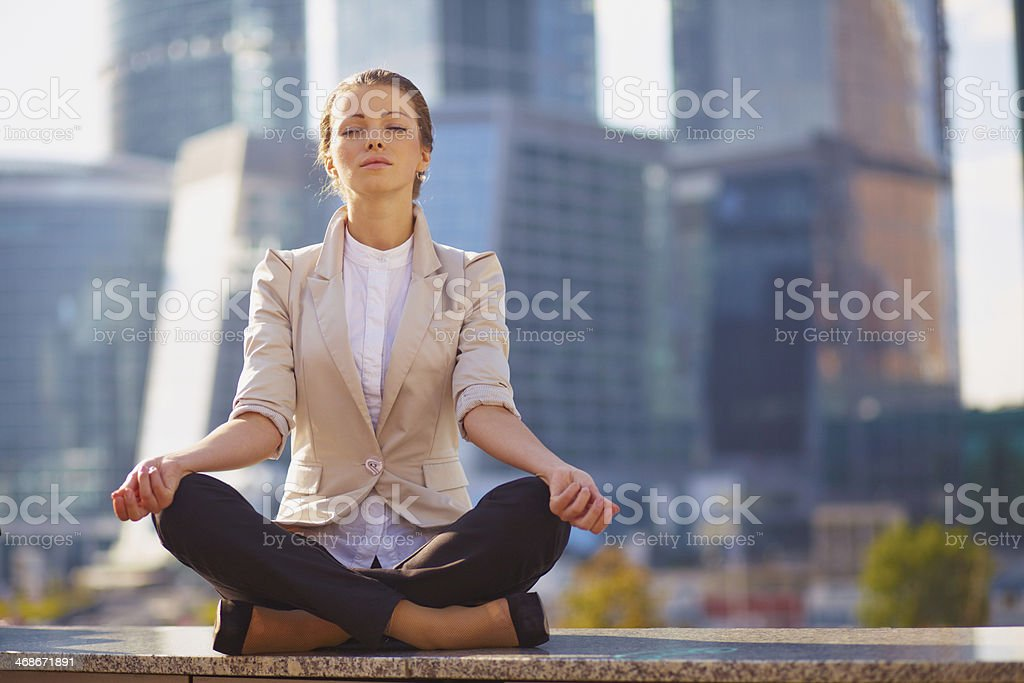 Business woman meditating outdoor over building background stock photo