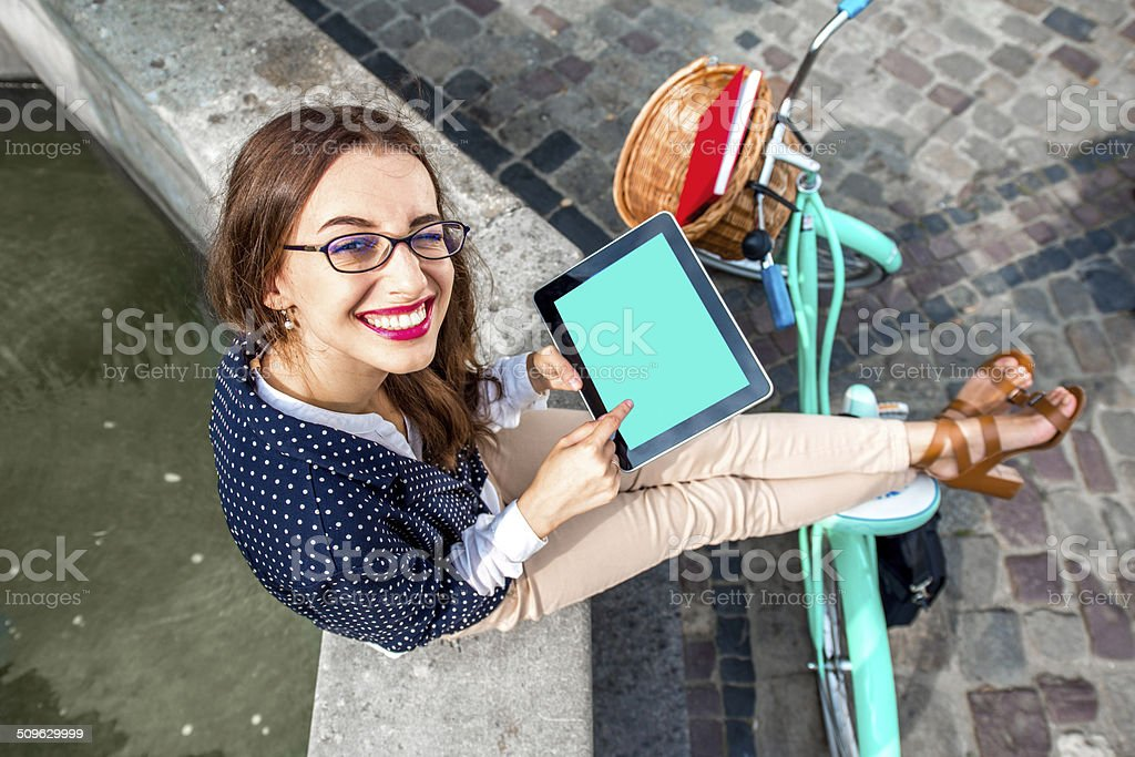 Business woman on bicycle using tablet stock photo