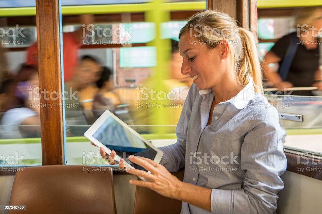 Business woman on cable car using digital tablet, Hong Kong stock photo
