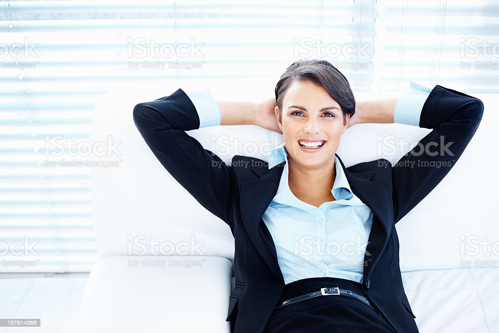 Business woman on couch with hands behind head royalty-free stock photo