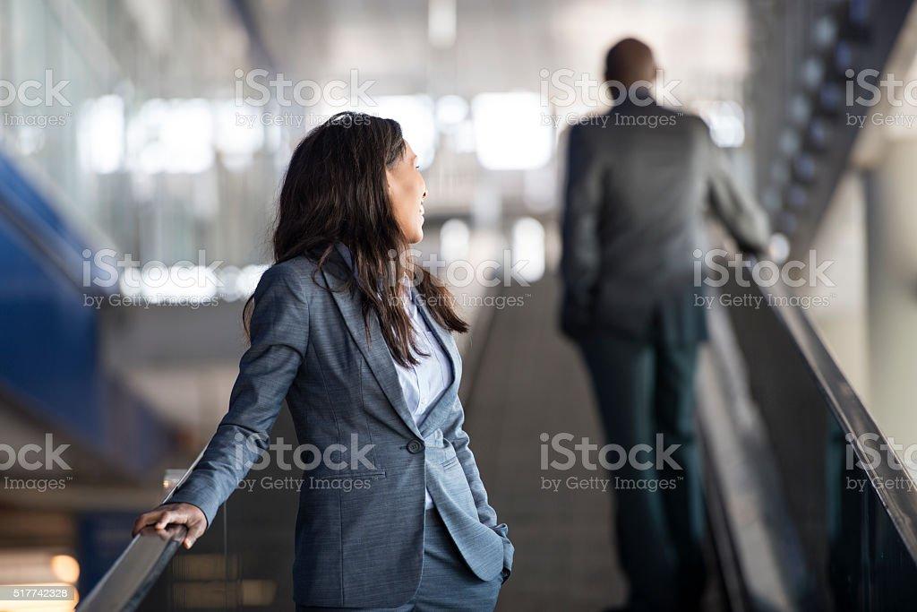 Business woman on escalator. stock photo
