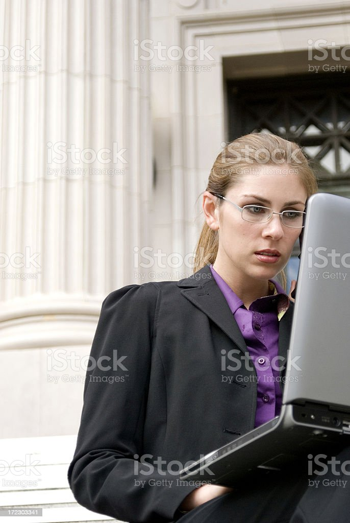 Business woman on laptop by columns royalty-free stock photo