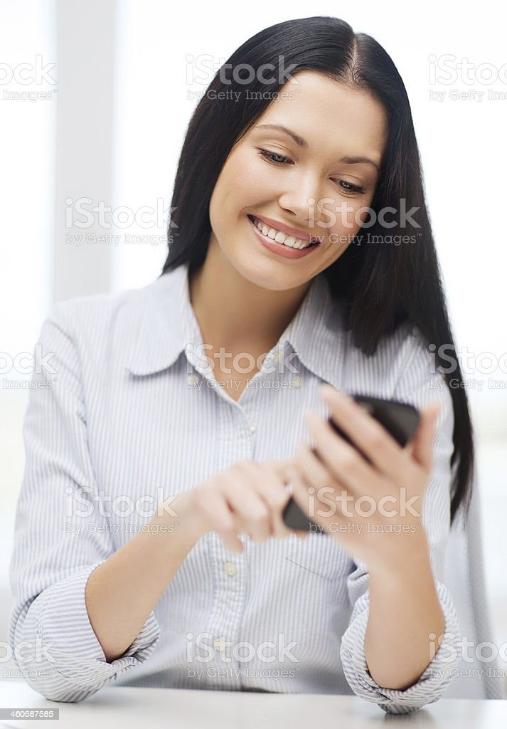 Business woman or student smiling while using a smartphone stock photo