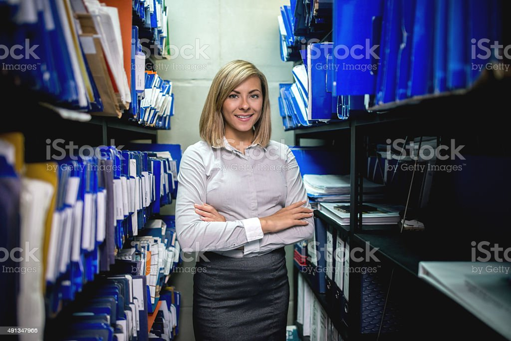 Business woman organizing the files in the filing cabinet stock photo
