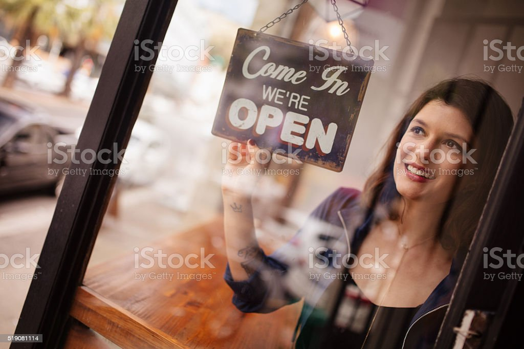 Business woman owner Turning Opening Sign on Door Coffee Shop stock photo