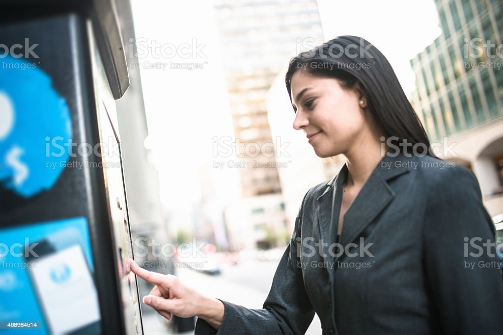 business woman paying th parking at the machine stock photo