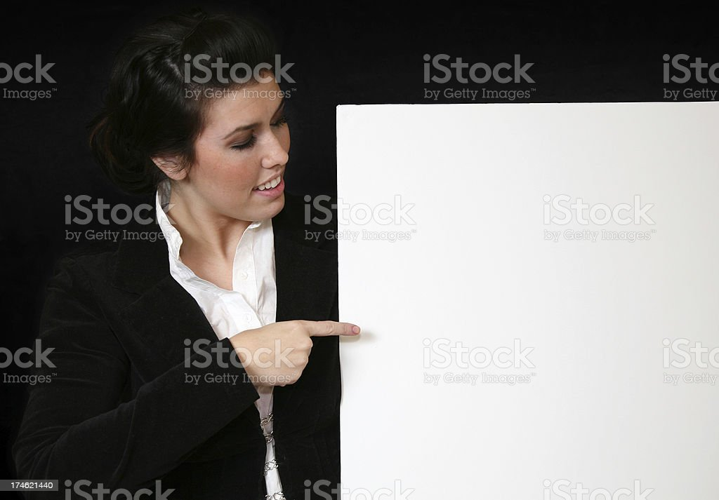 Business woman pointing to blank white sign royalty-free stock photo