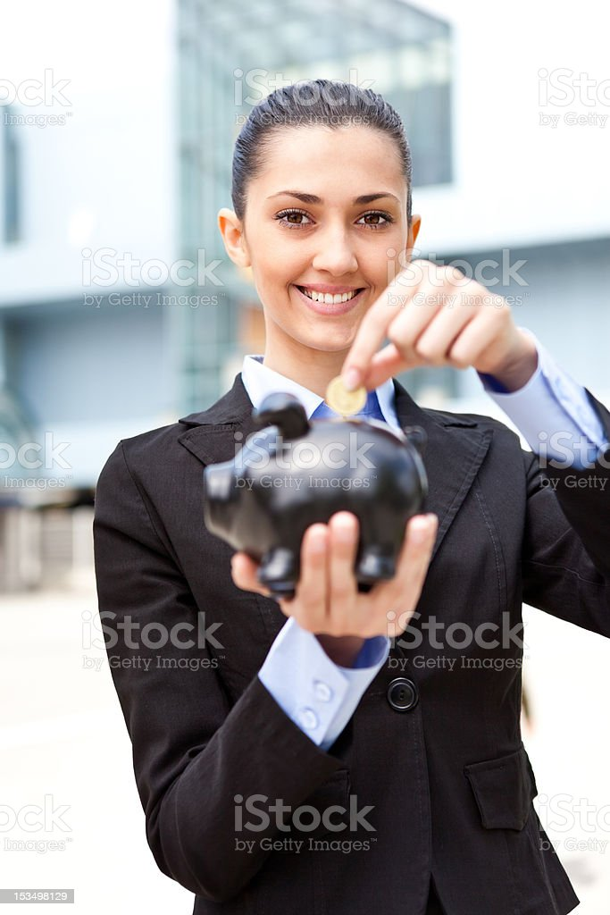 business woman putting coins money in piggy bank royalty-free stock photo