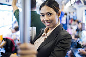 Business woman riding the elevated train in Bangkok.