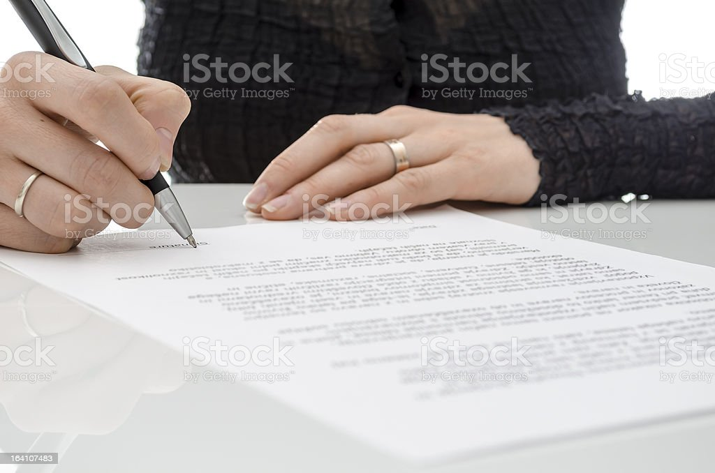 Business woman signing a contract above signature line royalty-free stock photo