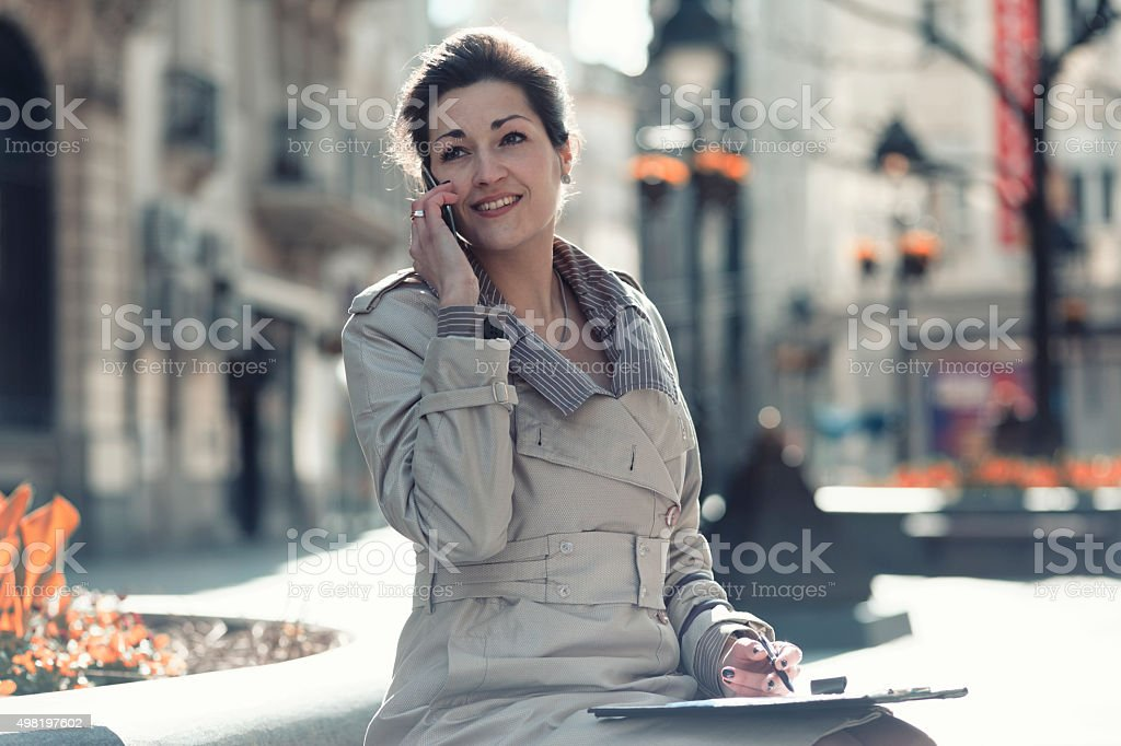Business woman sitting and talking on the phone and writing stock photo