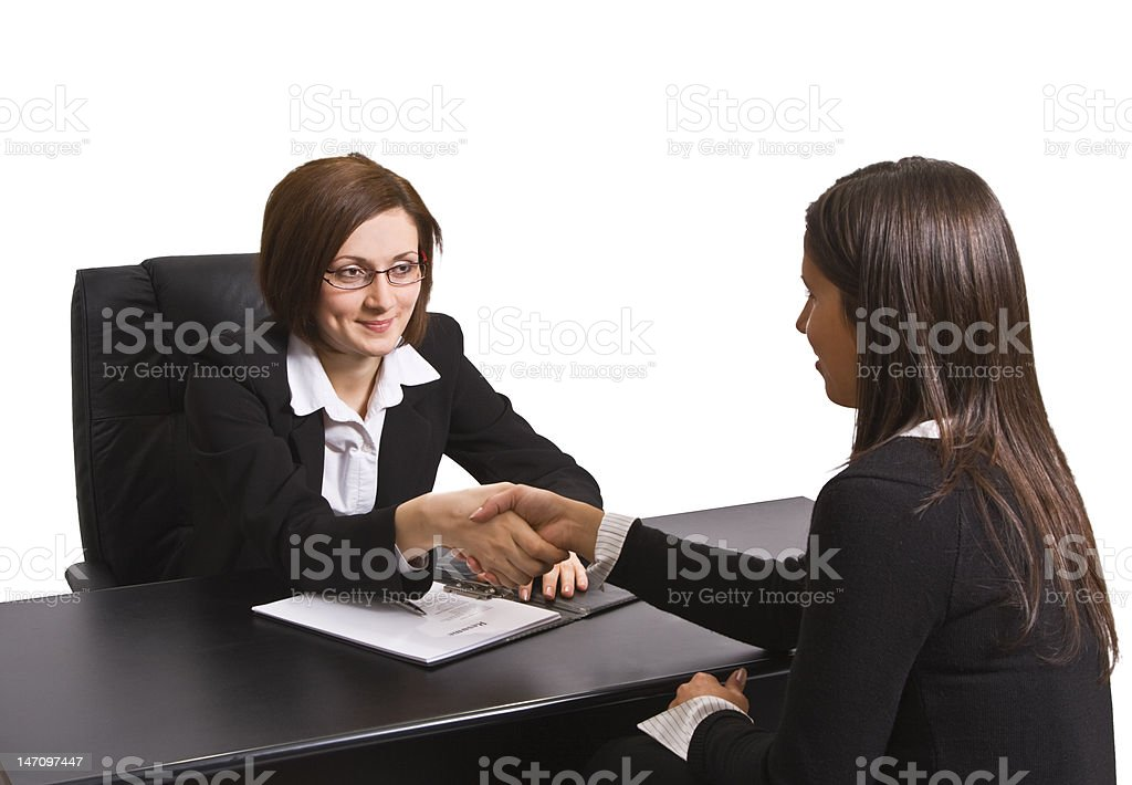 Business woman sitting at desk shaking hands with a woman. royalty-free stock photo